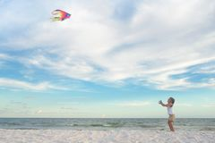 Happy girl flying kite on the beach Royalty Free Stock Images