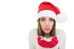 Happy girl with Santa beanie hat blowing snow Royalty Free Stock Image
