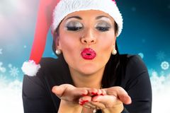 Happy girl with Santa Claus hat blowing snow Royalty Free Stock Image