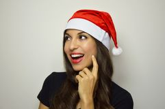 Happy girl with Santa Claus hat smiling and looks to the side your product on gray background. Copy space.  Royalty Free Stock Photo