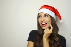 Happy girl with Santa Claus hat smiling and looks to the side your product on gray background. Copy space. Happy girl with Santa Claus hat smiling and looks to Royalty Free Stock Photo