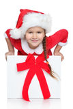Happy girl in Santa hat. Portrait of happy little girl in Santa hat looks out of Christmas gift box, on a white background Royalty Free Stock Photos