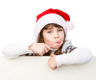 Happy girl in santa hat with Christmas candy cane standing behind white banner. isolated on white Royalty Free Stock Photos