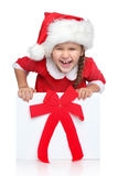 Happy girl in Santa hat looks out of gift box. Portrait of happy little girl in Santa hat looks out of Christmas gift box, on a white background Royalty Free Stock Images