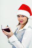 Happy girl in santa hat with a notebook Royalty Free Stock Photography