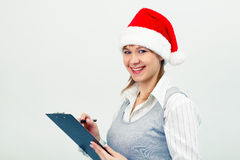 Happy girl in santa hat with a notebook Stock Image