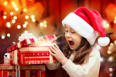 Happy Girl in Santa Hat Opening a Gift Box. Child in Santa hat with gift box Royalty Free Stock Photography