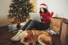 Happy girl in santa hat shopping online on laptop and sitting wi royalty free stock images