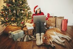 Happy girl in santa hat shopping online on laptop and sitting wi royalty free stock photography