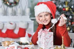 Happy girl in Santa hat sitting  with Christmas present stock images