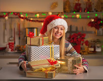 Happy girl in santa hat with stack of christmas present boxes Stock Images
