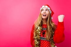 Happy girl in Santa hat and with tinsel on her neck, depicts a gesture of success and victory, on a red background. stock image