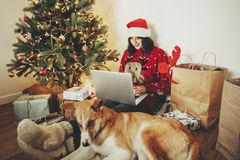 Happy girl in santa hat working on laptop and sitting with cute royalty free stock images