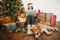 Happy girl in santa hat working on laptop and sitting with cute royalty free stock image