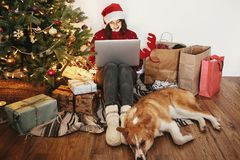 Happy girl in santa hat working on laptop and sitting with cute stock photos