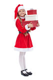 Happy girl in santa outfit holding presents Stock Images