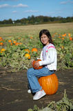 Happy girl sat on pumpkin Royalty Free Stock Image