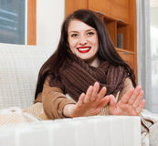 Happy girl in scarf  warming near warm heater Stock Image