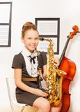 Happy girl in school dress with alto saxophone Royalty Free Stock Photos