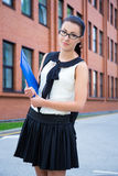 Happy girl in school uniform with backpack in campus Stock Image