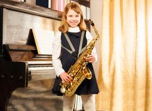 Happy girl in school uniform holds alto saxophone Royalty Free Stock Image