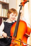 Happy girl in school uniform playing on the cello Stock Photography