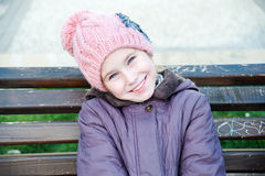 Happy girl-schooler sitting on bench in city park. Stock Image