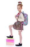 Happy girl schoolgirl holding his foot on a stack Stock Photo