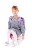 Happy girl schoolgirl sitting on books Stock Photography