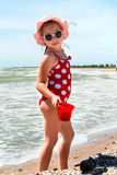 Happy girl at sea beach. Happy little child, adorable blonde toddler girl wearing colorful swimsuit playing on the beach Azov Sea making ice cream from sand Royalty Free Stock Photo