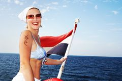 Happy Girl At Sea Travel. Beauty girl at the stern of the boat with a three color flag Stock Photography