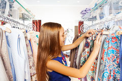 Happy girl searching for clothes during shopping Royalty Free Stock Photo