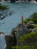 Happy girl on the seaside rock. Sea landscape wit active happy woman on the seaside rock with pine trees Stock Image