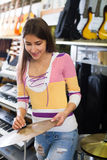 Happy girl selecting drums and accessories Stock Image