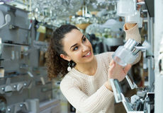 Happy girl selecting lighting units for interior Stock Photos