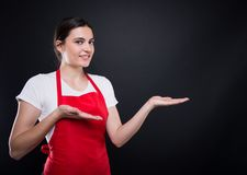 Happy girl seller with apron showing empty copyspace Royalty Free Stock Images