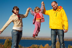 Happy girl shakes on hands at parents Royalty Free Stock Images