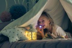 Girl shining a flashlight. Happy girl shining a flashlight at something stock photos