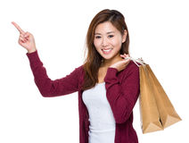 Happy girl with shopping bag and finger up. Asian woman isolated on white Royalty Free Stock Photo