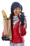 Happy girl with shopping bag and sandwich. Happy ethnic girl holding shopping bag, eating sandwich at wintertime Royalty Free Stock Images