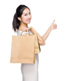Happy girl with shopping bag and thumb up. Isolated on white Stock Images