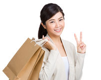 Happy girl with shopping bag and victory sign. Isolated on white Royalty Free Stock Photos