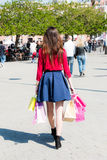 Happy girl with shopping bags in having fun. Nicely dressed girl is having a great time with some colorful bags after a long day of shopping, walking in public Stock Photography