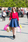Happy girl with shopping bags in having fun. Nicely dressed girl is having a great time with some colorful bags after a long day of shopping, walking in public Royalty Free Stock Image