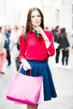 Happy girl with shopping bags in having fun. Nicely dressed girl is spinning and having a drink and a great time with some colorful bags after a long day of Royalty Free Stock Image