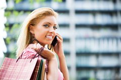 Happy girl with shopping bags having a phone call Royalty Free Stock Image