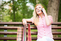 Happy girl with shopping bags having a phone call Stock Photos