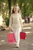 Happy girl with shopping bags walk in park. Kid shopper smile in fashion clothes outdoor. Little princess with crown on. Long blond hair. Child with paper bags royalty free stock images