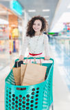 Happy girl with shopping carts in the mall. Happy girl with wavy curly hair with green shopping carts in the mall. Kraft bags with purchases. Make purchases Royalty Free Stock Images