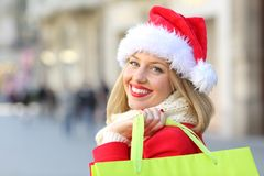 Happy girl shopping in christmas looking at you. Portrait of a happy girl wearing santa claus hat shopping in christmas looking at you outdoors on the street Stock Image